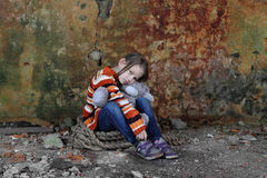 Little girl sits in basement with teddy bear in hands Royalty Free Stock Images