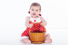 Little girl sits with basket cherries stock photos