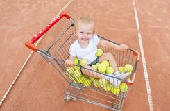 The little girl sits in a basket for tennis balls. View from above Royalty Free Stock Image