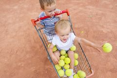 The little girl sits in a basket for tennis balls. Small children play in the tennis court. View from above Stock Photography