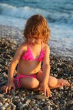 Little girl sits on beach Royalty Free Stock Images