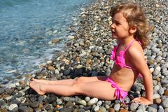 Little girl sits on beach Royalty Free Stock Photos