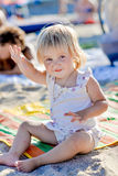A little girl sits on the beach in the sand and smiles royalty free stock image