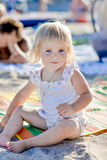 A little girl sits on the beach in the sand and smiles royalty free stock photos