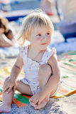 A little girl sits on the beach in the sand and smiles stock image
