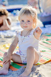 A little girl sits on the beach in the sand and smiles royalty free stock images