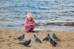Little girl sits on beach at water edge in autumn Stock Photo