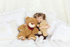 Little girl sits bed with pillows and teddy bears Royalty Free Stock Photo
