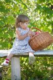 Little girl sits on a bench Stock Photo