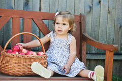 Little girl sits on a bench Royalty Free Stock Photo