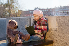 Little girl sits on a bench. And reads the book to a toy bear Stock Photos