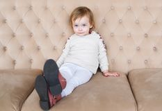 Little girl sits on a brown sofa indoors. royalty free stock image