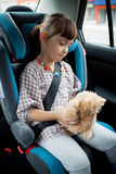 The little girl sits in a car Stock Image