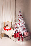 Little girl sits in a chair near the Christmas Royalty Free Stock Images