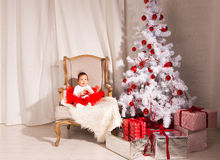 Little girl sits in a chair near the Christmas Stock Photography