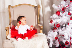 Little girl sits in a chair near the Christmas Stock Image