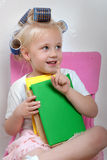 The little girl sits on a chair whith hair curlers on her head Royalty Free Stock Images