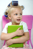 The little girl sits on a chair whith hair curlers on her head Stock Photo