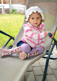 The little girl sits in a chaise lounge on the garden site.  royalty free stock photo