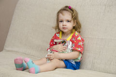 The little girl was sitting on the sofa with scarves in the hands of Royalty Free Stock Photo