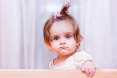 Little girl sits in the crib Stock Photos