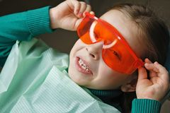 Little girl in dental clinic. Little girl sits in dental chair and wears protective glasses. She dabbles stock image