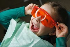 Little girl in dental clinic. Little girl sits in dental chair and wears protective glasses. She dabbles royalty free stock photo