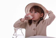 A little girl sits and drinks water from a glass Royalty Free Stock Photos