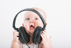 The little girl sits in ear-phones Royalty Free Stock Images