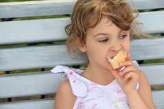 Little girl sits and eats ice-cream Royalty Free Stock Photo