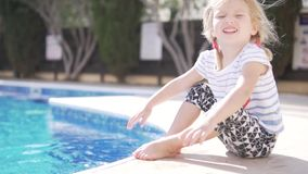 A little girl sits at the edge of the pool stock footage