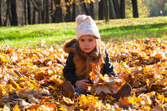 Little girl sits on fallen leaves Stock Photography