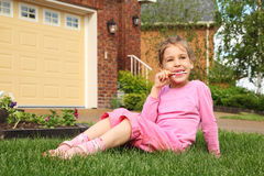 Little girl sits and finishes eating ice cream. Little girl sits on green grass near cottage and finishes eating ice cream stock images