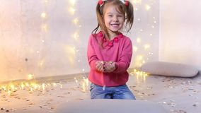 Little girl sits on floor and holds in hands festive confetti. Little dark-haired girl sits on floor in photo studio and holds in hands Christmas confetti stock video