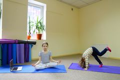 Little girl sits on floor in lotus position. royalty free stock image