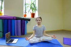 Little girl sits on floor in lotus position. stock photography