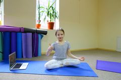 Little girl sits on floor in lotus position. stock photo