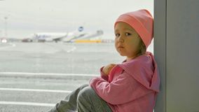 Little girl sits on the floor next to window at airport and looks at camera. Portrait of little baby girl sits on the floor next to window at airport and looks Royalty Free Stock Image