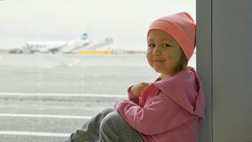 Little girl sits on the floor next to window at airport and looks at camera. Portrait of little baby girl sits on the floor next to window at airport and looks Royalty Free Stock Photography