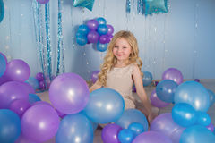 Little girl sits on a floor of a studio with a lot of color balloons. Pretty little girl sits on a floor of a studio with a lot of color balloons Royalty Free Stock Image