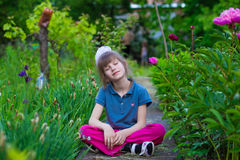 Little girl sits in flowers in the park and dream. In summer day Stock Photos