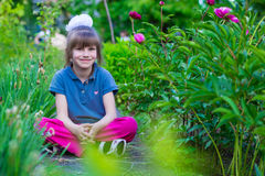 Little girl sits in flowers in the park Royalty Free Stock Image