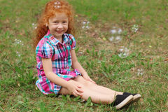Little girl sits on grass among bubbles in summer Stock Image