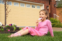Little girl sits on grass and eats ice cream. Little girl sits on green grass near cottage and eats ice cream stock image