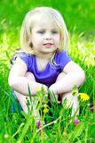 Little girl sits in a grass outdoors Stock Photo