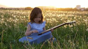 Little girl sits in the grass and plays the jeans guitar. in the dandelions field spring bloom at sunset. concept music in nature. Cute little girl sits in the