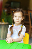 Little girl sits in at green table Stock Photography