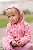 Little girl sits on ground with a piece of chalk Stock Images