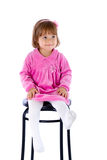 The little girl sits on a high chair. Isolated on a white background Royalty Free Stock Image