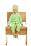 The little girl sits on a high chair Stock Photography